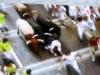 En tjurrusare trillar omkull och blir sen översprungen av tjurarna.