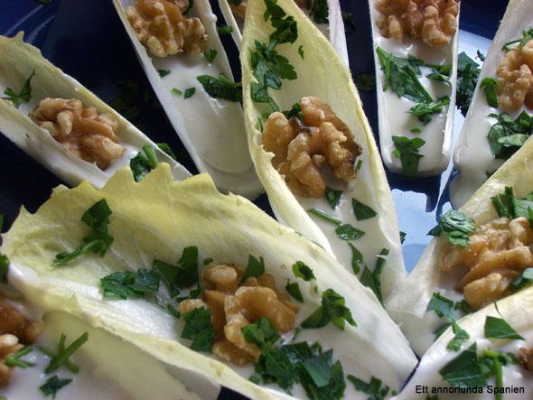 Häll ostblandningen i en skål och placera endivbladen runt om, eller fyll endiverna med ostblandningen innan serveringen. På bilden ovan är de garnerade med valnötskärnor och klippt bladpersilja.